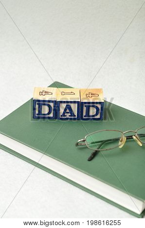 Dad spelled with colorful blocks with a book and glasses