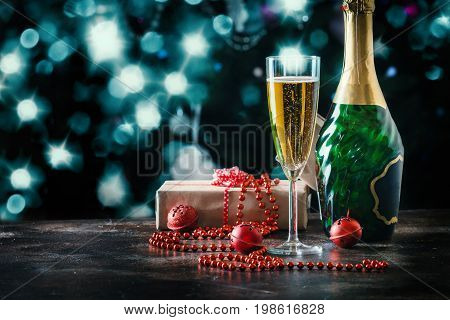 champagne glass and bottle over bokeh and Christmas tree as a background