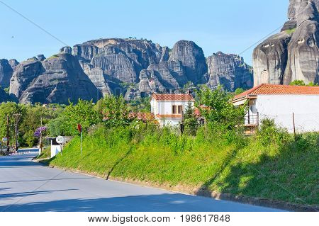 White houses in Kastraki village and the road under the rocks with Meteora monastery, Greece