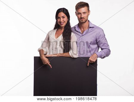 Young happy woman portrait of a confident businesswoman showing presentation, pointing placard gray background. Ideal for banners, registration forms, presentation, landings, presenting concept.