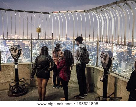 Tourists And Binoculars On Top Of Empire State Building At Night In Manhattan, New York