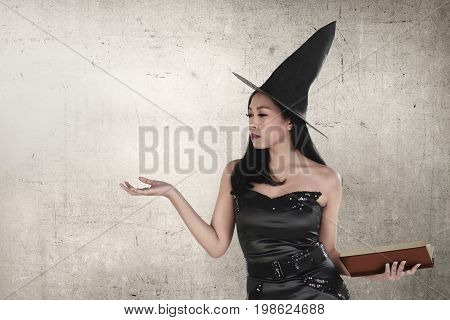 Young Asian Witch Woman With Hat Holding Spell Book