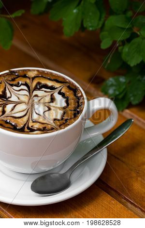 Coffee cup of cappuccino. Hot Cappuccino coffee with zigzag caramel motif or spiderweb art floating on top on wooden background. Close up