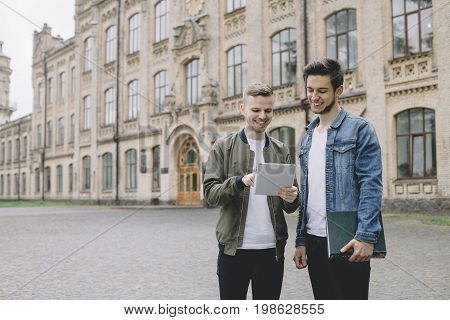 Two guys are standing aside the university's building. The dark-haired guy is holding a book in his hands. The other one is holding a laptop in his hand and showing his friend an interesting information.