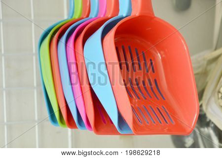 colorful plastic cat litter shovel hanging on hook displays in pet shop