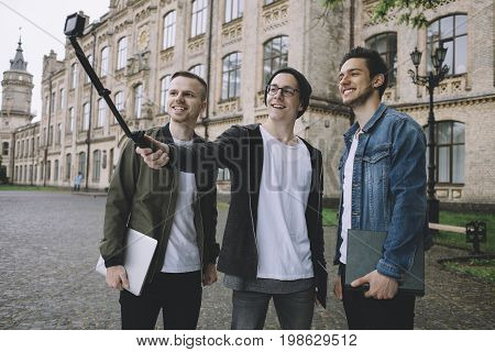 Three students are standing outside of university's building and taking selfie using a selfie stick during the short break between lessons.