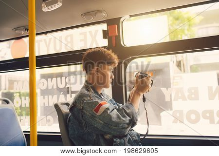 Asian male traveller taking photo of the city from the window of the bus