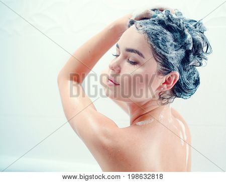 Washing hair. Beautiful naked young woman is smiling and using shampoo while taking shower in bathroom. beauty sexy model girl washing her long black hair