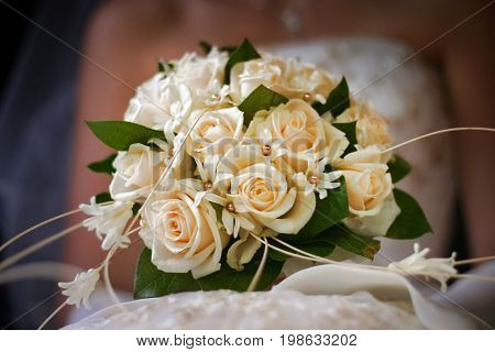 Wedding bouquet from beige roses on a background of a wedding dress