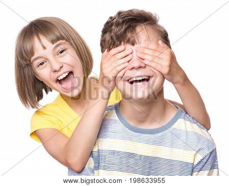 Teen girl covering boy's eyes to surprise his. Portrait of brother and sister isolated on white background. Funny couple children laughing with a perfect smile.