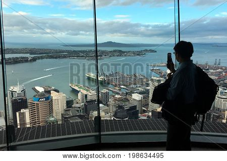 AUCKLAND - AUG 03 2017:Visitor take photo with his mobile phone from Auckland's Sky Tower observation deck. In 2016 Auckland hosted a record total of 2.217 million international visitors.