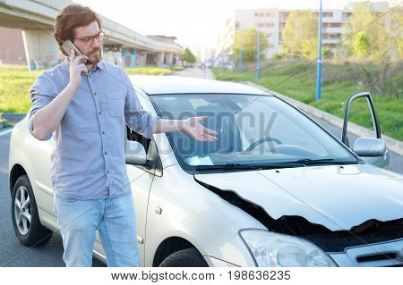 Man calling help after a car crash accident on the road