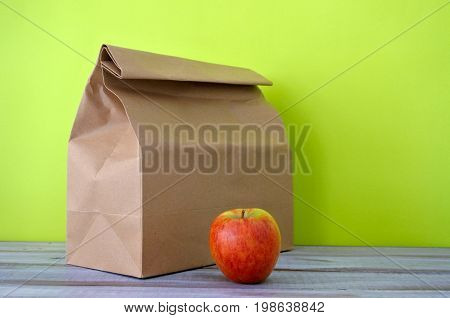 Lunch Packed In A Brown Paper Bag With Red Apple