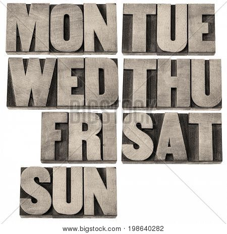7 days of week (first 3 letter symbols) in isolated vintage wood letterpress printing blocks, black and white warm toned image