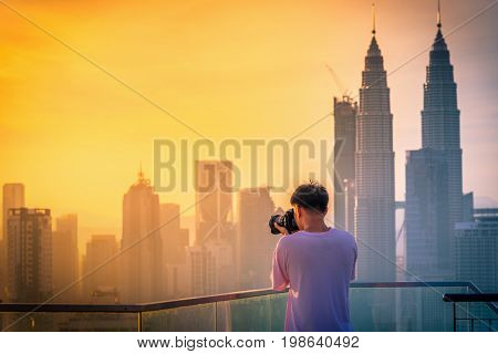 Photography take photo of Kuala lumpur city skyline on the roof top of hotel at sunrise in Malaysia.