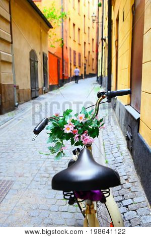 Bicycle with daisy flowers on handle bar in old street in Stockholm, Sweden