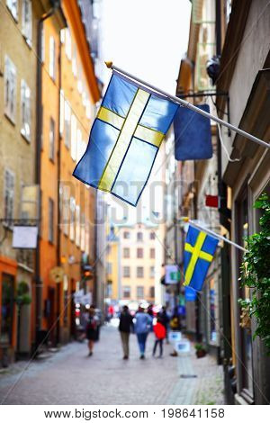 Perspective of old street in Stockholm with swedish flags, Sweden. Shallow DOF, focus on the first flag