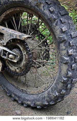 A fragment of a dirty motorcycle wheel