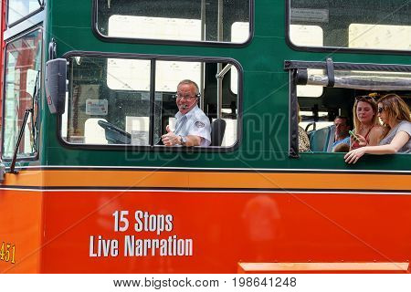 NASHVILLE TN USA - APRIL 14 2017: Shot in Nashville cheerful sightseeing tour bus driver giving thumbs up with tourists near open windows checking smartphone and occasionally the sights. This scene repeats every day in innumerable tourist destinations thr