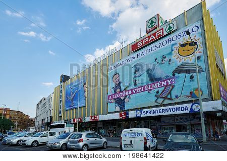 BUDAPEST HUNGARY - JUNE 3 2017: Busy street corner in Budapest with building-size billboard attached to yellow frame building in the Corvin Club area on Rakoczi Ut.