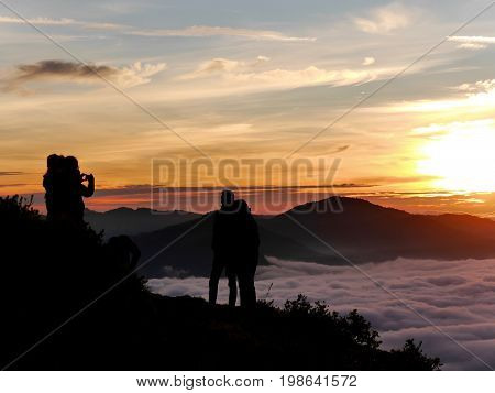 A couple pose for a photo in front of an awesome sunrise by tone of the three differently coloured crater lakes of Kelimutu volcano, Flores, Indonesia