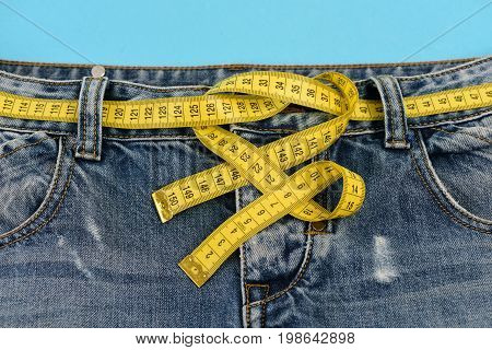 Blue jeans with yellow measure tape instead of belt. Healthy lifestyle and dieting concept. Top part of denim trousers isolated on blue background. Close up of jeans with measure tape around waist.