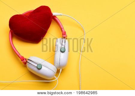 Headset for music and heart shaped player. Music accessories and Valentines day concept. Modern earphones isolated on light orange background copy space. Headphones in white and red color with heart