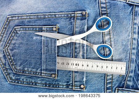 Tailoring and design concept. Metal scissors and ruler in denim pants pockets. Tailors tools with denim fabric. Things for making clothes in back pockets of jeans top view.