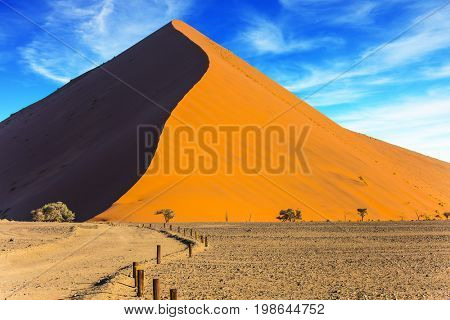 The concept of extreme and exotic tourism. The Namib-Naukluft at sunset. Sharp border of light and shadow over the crest of the dune. Namibia, South Africa