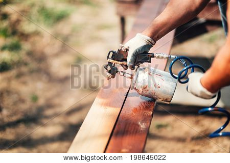 Construction Worker Using Paint Gun And Brown Paint During Renovation Works. Painting Fence