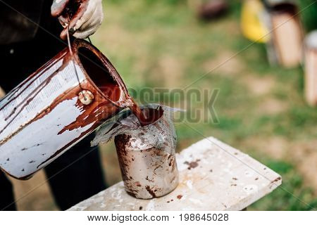 Construction Worker Wearing Protective Gloves Pouring Liquid Paint Into Spray Gun For Painting Woode