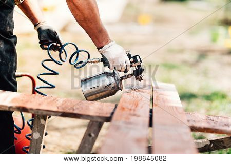 Industrial Man Painting Brown Timber, Renovating Exterior Fence During New House Design