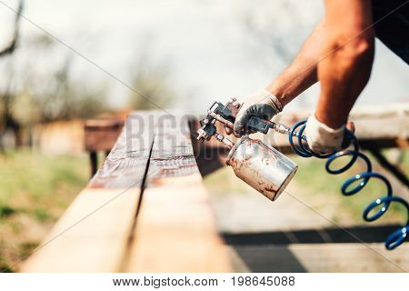 Man Painting Wooden Timber With Brown Color During Renovation Works