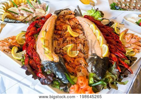 Shrimp, Crayfish, Salmon on a buffet table decorated with lemon, on a white plate.
