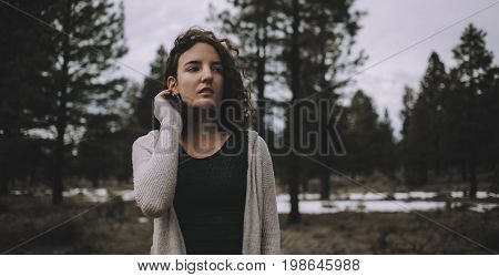 Smiling and nice caucasian girl in a warm cardigan standing outdoors in nature at day time. She is enjoying with this cold but pleasant day. Close up