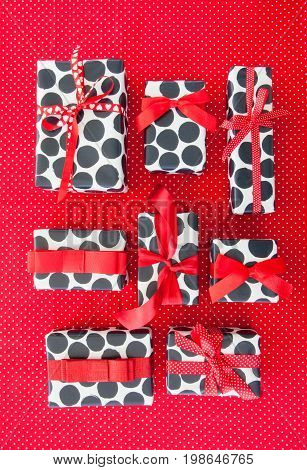 Little presents with red ribbons on red polka dot background