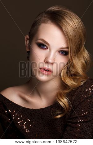 Portrait of beautiful young woman with professional evening makeup, perfect skin, wavy hairstyle on brown background. Hollywood style