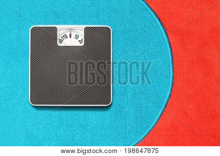 Bathroom scale on blue and red carpet. Background for leaflets and web sites on slimming and dieting theme.