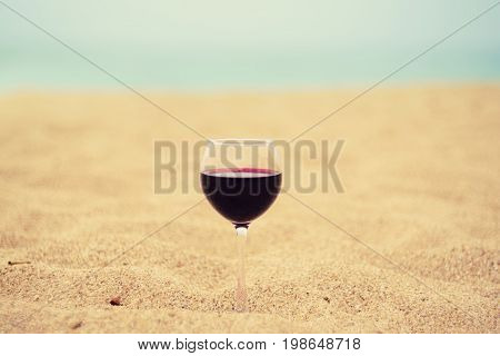 A glass of red wine on the sand at the sea coast. Vacation pleasure concept