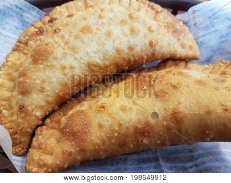 two delicious flaky fried golden brown empanadas