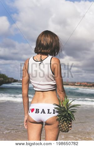 Sexy tropical woman butt close up with exotic pineapple fruit on the beach of paradise island of Bali, Indonesia.