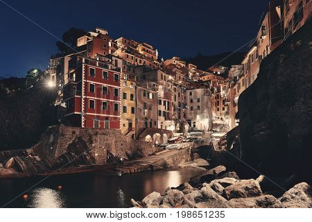 Riomaggiore waterfront view with buildings in Cinque Terre at night, Italy.