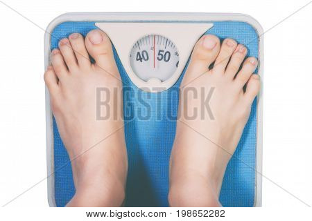 legs of a young woman measuring her weight on a bathroom scale