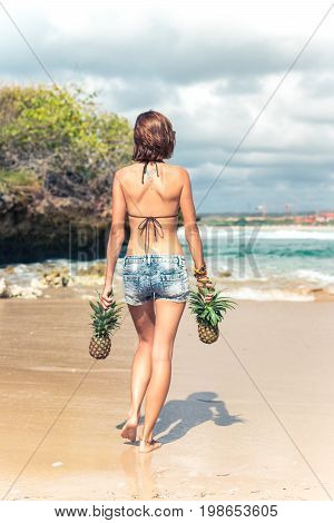 Sexy tropical woman butt close up with exotic pineapple fruit on the beach of paradise island of Bali. Healthy diet concept. Indonesia.