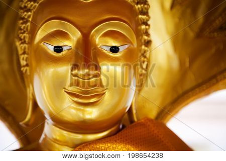 Golden peaceful Buddha statue smiling peaceful face. Religious yellow sculpture at Buddhist shrine in Thailand