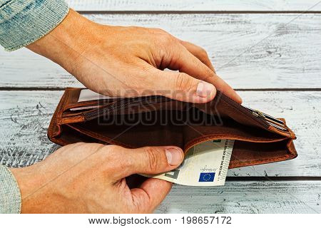 Male hands in worn jeans jacket holding old leather wallet with just five euro note - poverty concept