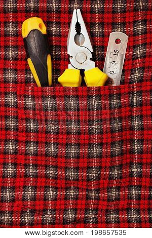 Some hand tools - pliers screwdriver and ruler - in classic work checkered shirt pocket - close up caption - labour day concept