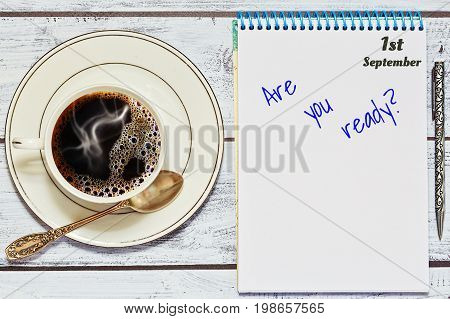 Coffe and reminder notebook with text on the table in top view - beginning or academic or business year concept
