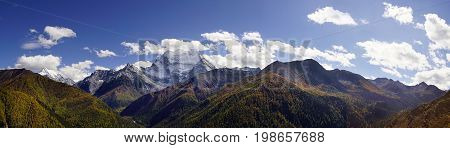 Shangri La, A Panorama View Of Holy Snow-clad Mountain Chanadorje And Yellow Orange Colored Autumn T