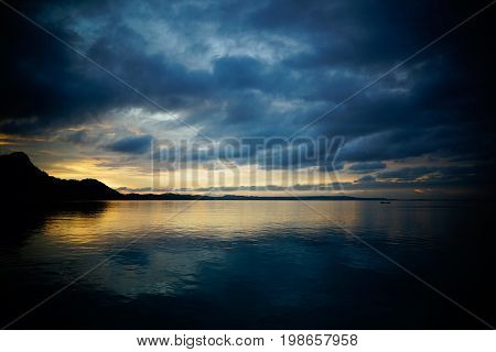 Silhouette of small boat with one person under dark blue stormy sky of clouds going towards island in the asian ocean at nightfall during yellow sunset.